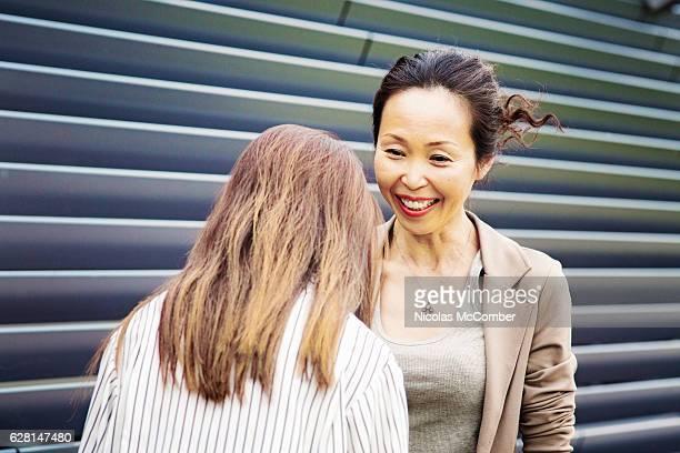 Kind Japanese teacher smiles at repentant pupil