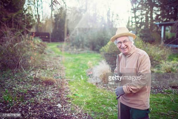 freundlicher alter herr gärtnert im frühjahr - aktiver lebensstil stock-fotos und bilder