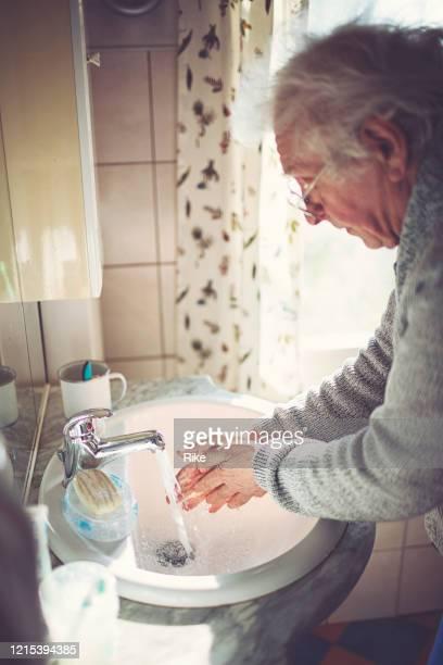 freundlicher alter herr wärst seine hände mit seife am waschbecken - nordeuropäischer abstammung stock-fotos und bilder