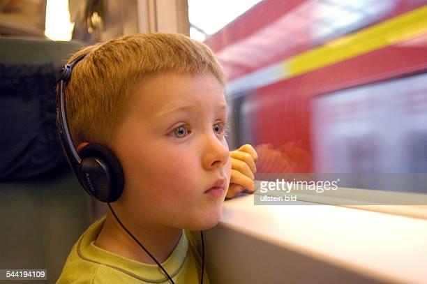 Kind schaut aus dem ICE Zug Fenster Kopfhörer Hörspiel Kind Reise model released