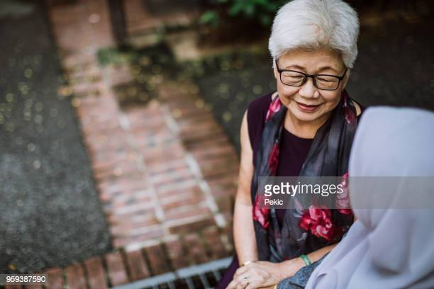 kind talk between grandma and granddaughter - chubby granny stock pictures, royalty-free photos & images