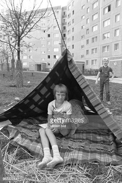Kinder haben sich auf einer Wiese vor Plattenbauten im Wohngebiet ErnstThälmannPark in Berlin aus Decken ein Zelt gebaut aufgenommen 1985 Das...