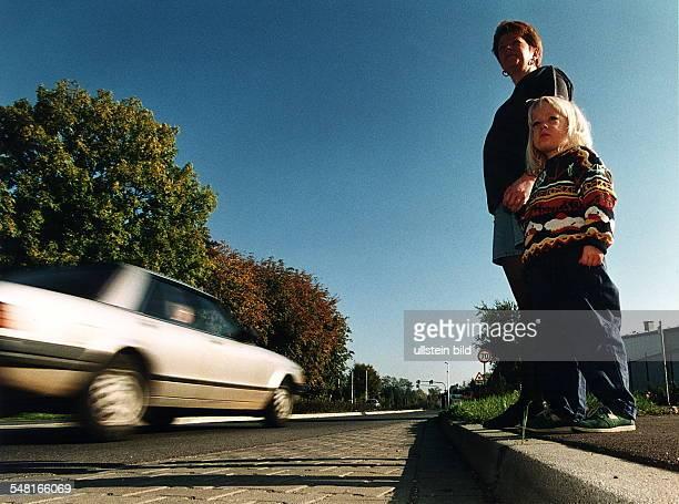 Kinder im Straßenverkehr: ein kleines Mädchen wartet an der Hand ihrer Mutter ein vorbeifahrendes Auto ab, um die Straße überqueren zu können. -...