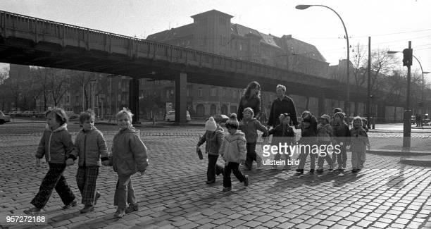 Kinder laufen mit ihren Betreuerinnen auf der Schönhauser Allee in BerlinPrenzlauer Berg und gehen bei Grün über eine Ampel aufgenommen 1980