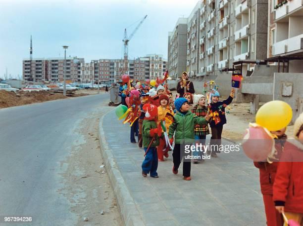 Kinder laufen mit kleinen bunten Papierfahnen und Luftballons auf einem Gehweg im Neubaugebiet RostockSchmarl undatiertes Foto von 1978 Zwischen 1976...