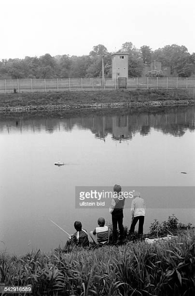 Kinder spielen mit einem ferngesteuerten am Teltowkanal, im Hintergrund ein Wachturm an den Grenzanlagen der DDR- April 1984