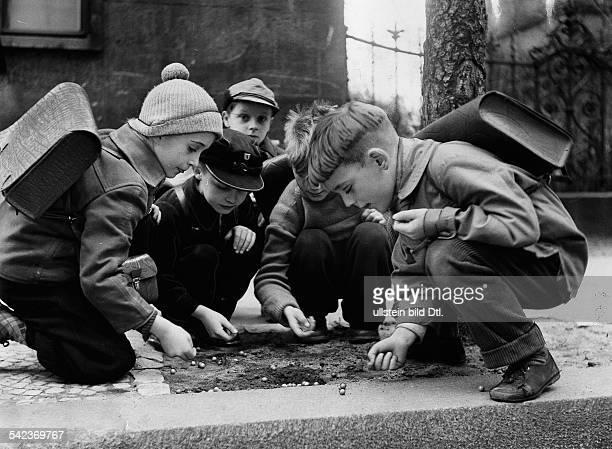 Kinder spielen nach Schulschlussmit den Murmeln auf dem GehwegBerlin 1958