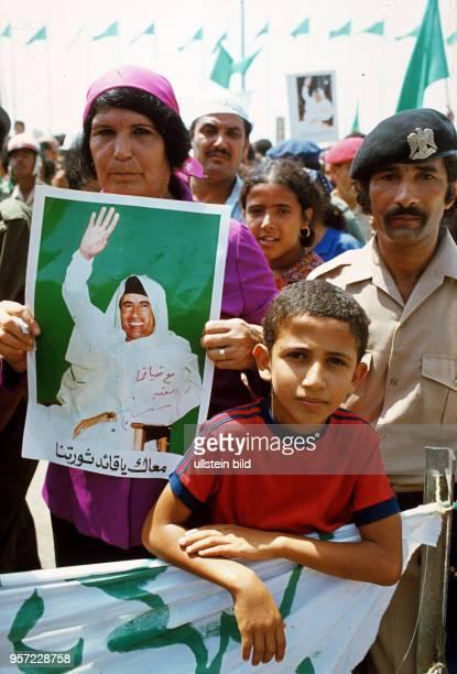 Kinder und Erwachsene mit Fotos des Revolutionsführers Oberst Gaddafi aufgenommen im September 1979 an einer Straße in der libyschen Stadt Bengasi...