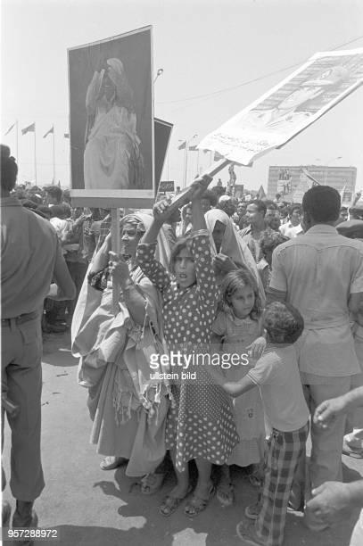 Kinder und Frauen mit Bildnissen des libyschen Revolutionsführers Gaddafi unter den Zuschauern bei einer Militärparade in Bengasi im September 1979...