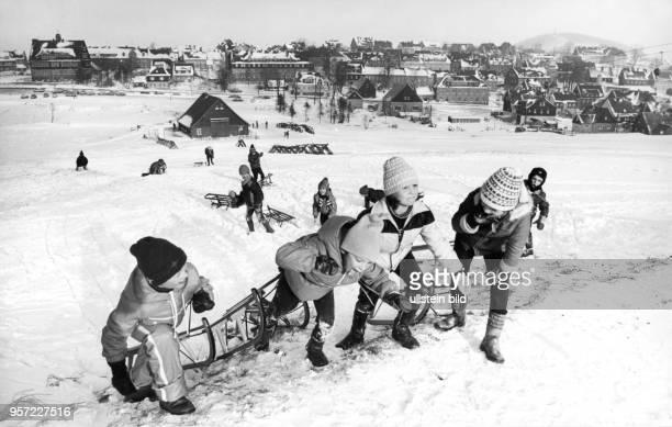 Kinder ziehen ihre Schlitten einen Rodelberg hinauf und freuen sich über den vielen Schnee aufgenommen 1978 im osterzgebirgischen Altenberg Sie...