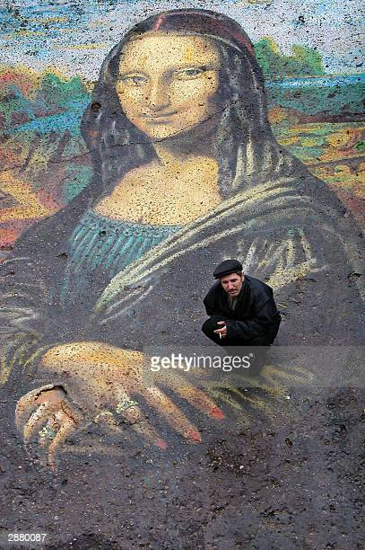 Kindergarden keeper Leonid Lebedenko poses with a giant copy of Leonardo da Vinci's Mona Lisa he painted on the asphalt in his appartment block...