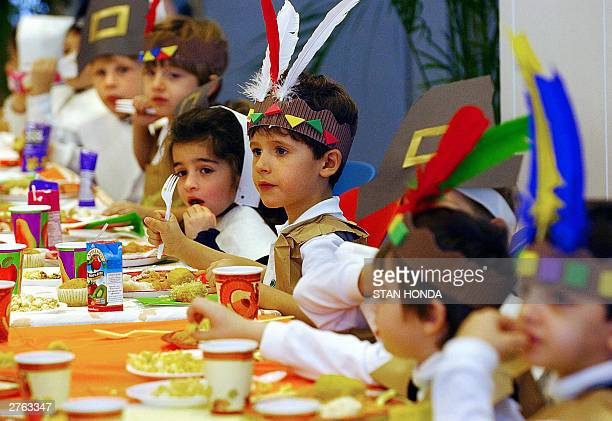 Kindergarden students wearing costumes depicting Native Americans and Pilgrims eat during a Thanksgiving eve lunch 26 November at the Lycee Francais...