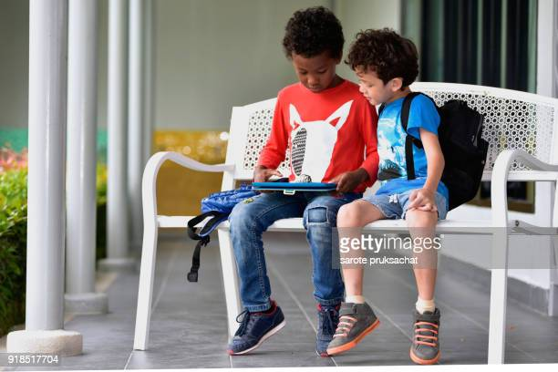 Kindergarten boys  play game in tablet together in an international school park, technology, outdoor, computer, internet concept .