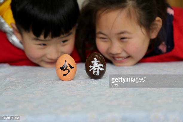 Kindergarten children balance their eggs on end on the Spring Equinox day on March 21 2018 in Lianyungang Jiangsu Province of China The old legend...