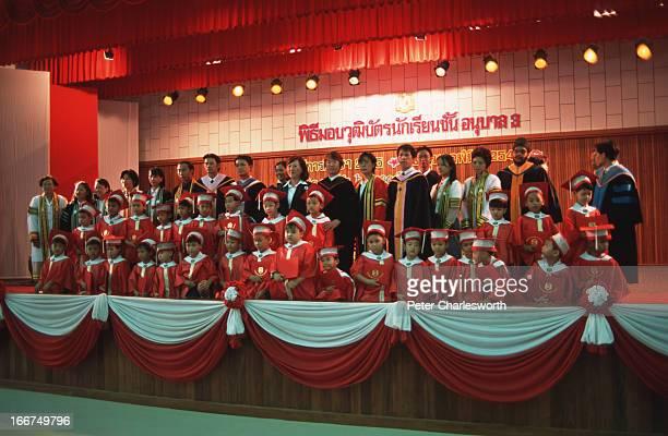 Kindergarten children dressed in full graduation regalia including mortar boards at the endofterm graduation ceremony Thailand's education system is...