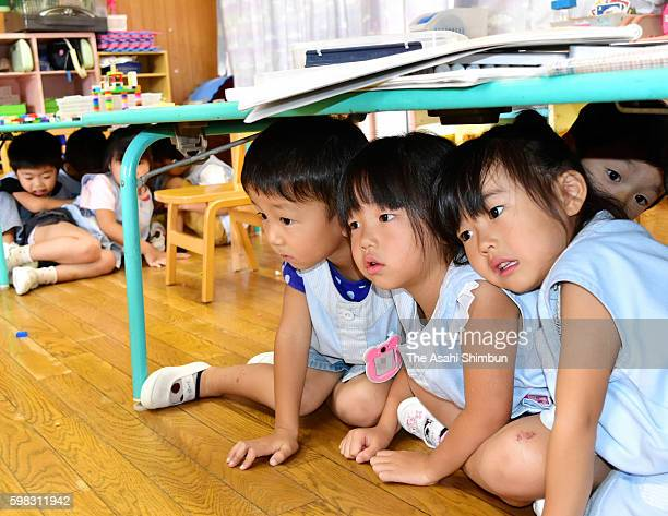 Kindergarten children evacuate under tables during an emergency drill on September 1 2016 in Toyama Japan emergency drills are held across the nation...