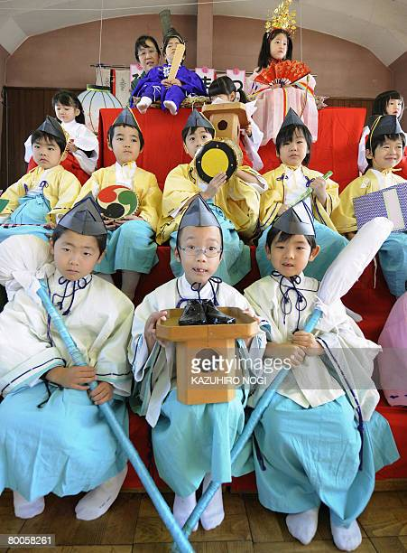 Kindergarten children in traditional costumes and tiaras smile as they pose on a platform for hinamatsuri or doll festival at Tokyo's Mukojima Bunka...