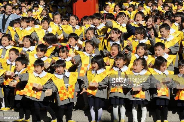 Kindergarten children throw beans to drive away evils and bring good luck at the annual Setsubun festival at the Sensoji temple in Tokyo on February...