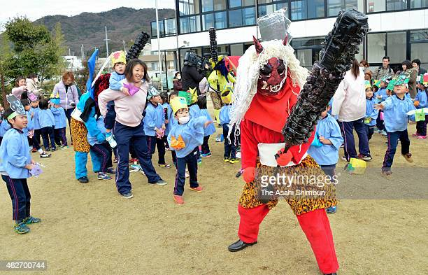 Kindergarten children throw beans toward ogre during a beanscattering ceremony on February 3 2015 in Himeji Hyogo Japan The ceremony is held all over...