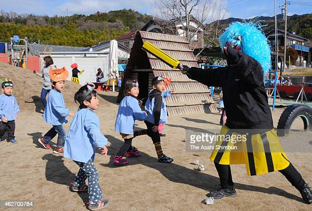 Kindergarten children throw beans toward ogre during a beanscattering ceremony on February 3 2015 in Yanai Yamaguchi Japan The ceremony is held all...