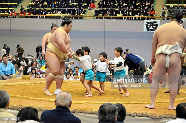 Kindergarten children try to push a sumo wrestler during the Grand Sumo Tour on December 3 2013 in Tosu Saga Japan