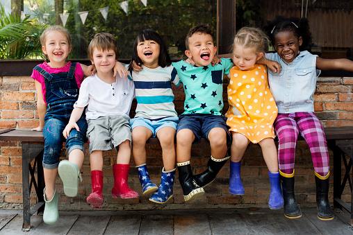 Kindergarten kids friends arm around sitting smiling 685864090