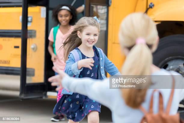 Kindergarten schoolgirl runs to her mom after school