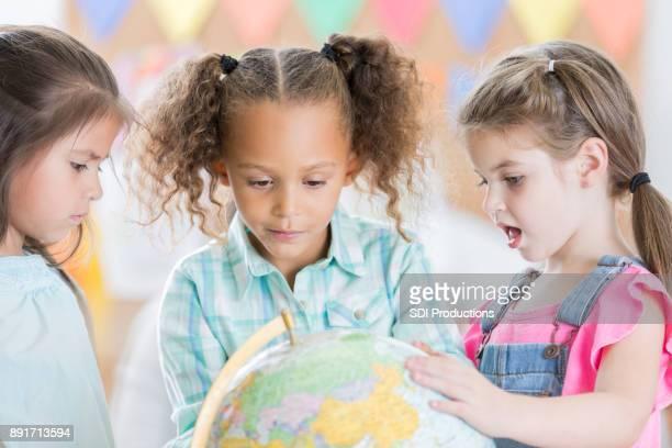 Kindergarten Schulmädchen betrachten Globus zusammen