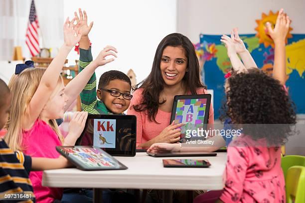 Kindergarten students and teacher using digital tablets