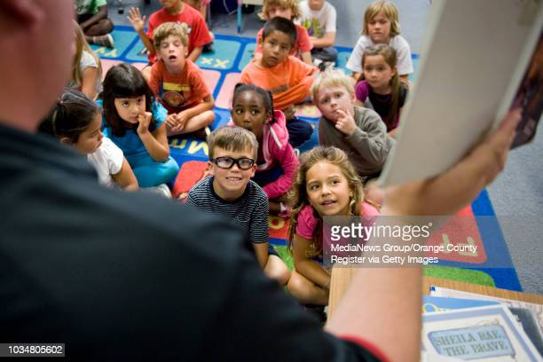 Kindergarten students at Davis Magnet School in Costa Mesa listen as teacher James Christman reads to them Davis Magnet received a statewide API rank...