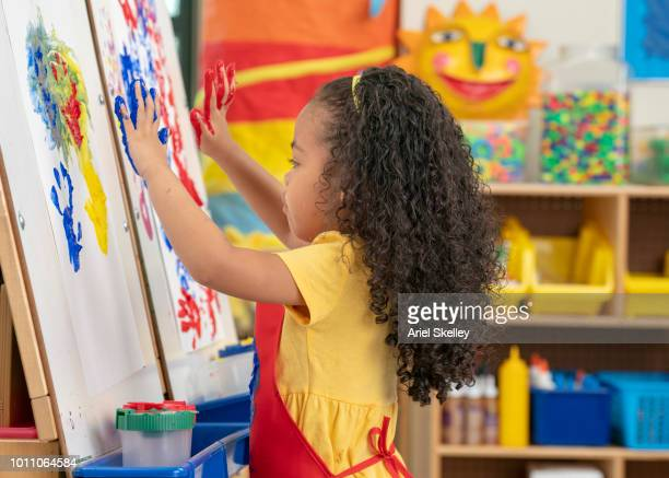 kindergarten students finger painting - 4 girls finger painting stock photos and pictures