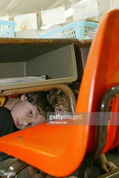 Kindergarten students hide under their desks during a classroom lockdown drill February 18 2003 in Oahu Hawaii Lockdown procedure is used to protect...