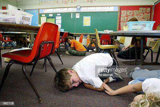 Kindergarten students lie on the floor during a classroom lockdown drill February 18 2003 in Oahu Hawaii Lockdown procedure is used to protect school...