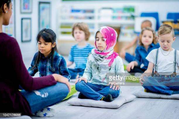 kindergarten students meditate in class - mindfulness stock pictures, royalty-free photos & images
