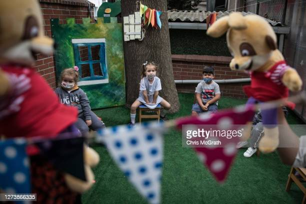 Kindergarten students wearing protective face masks watch a puppet show perfomed by their teachers at the Florya Ugur College on September 21, 2020...