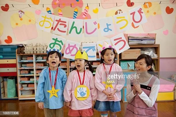 Kindergarten Teacher and Children Celebrating Birthday