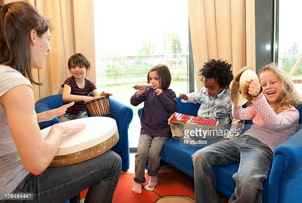 Kindergarten teacher and children making music