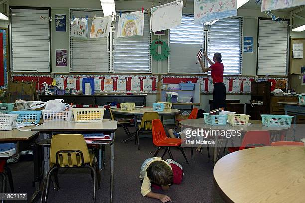 A kindergarten teacher closes the windows as her students crawl under their desks during a classroom lockdown drill February 18 2003 in Oahu Hawaii...