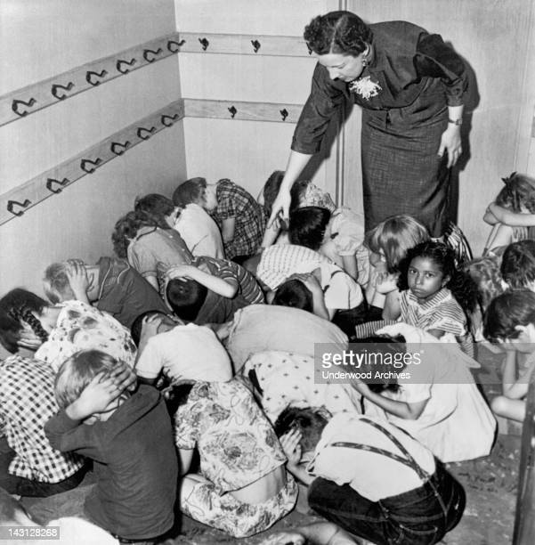 A kindergarten teacher coaches a group of crouched children to duck and cover in a national air raid drill Chicago Illinois 1954