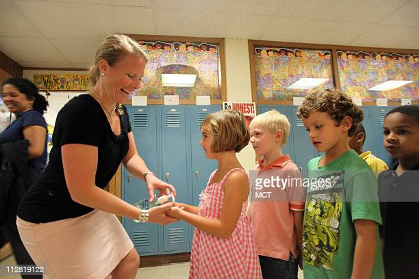 Kindergarten teacher Courtney Dohman dishes out a squirt of hand sanitizer to Nora Hartman as classmates wait their turn at Holmes elementary School...