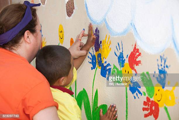 kindergarten teacher helps a young boy paint a colorful mural using his handprint. - explaining stock pictures, royalty-free photos & images