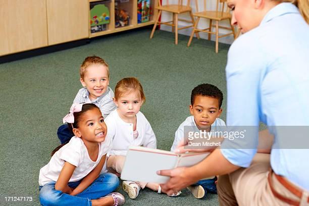 Kindergarten teacher in class reading to students