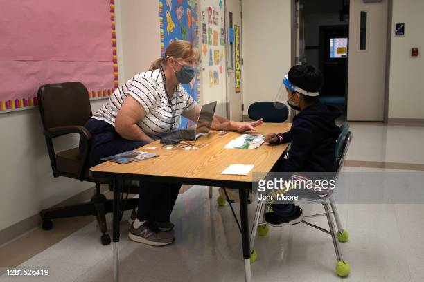 Kindergarten teacher Maggie Peterson reaches around a safety shield while giving a reading test to a student at Stark Elementary School on October...