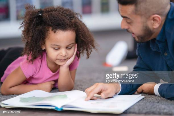 kindergarten teacher reading book to student - montessori education stock pictures, royalty-free photos & images
