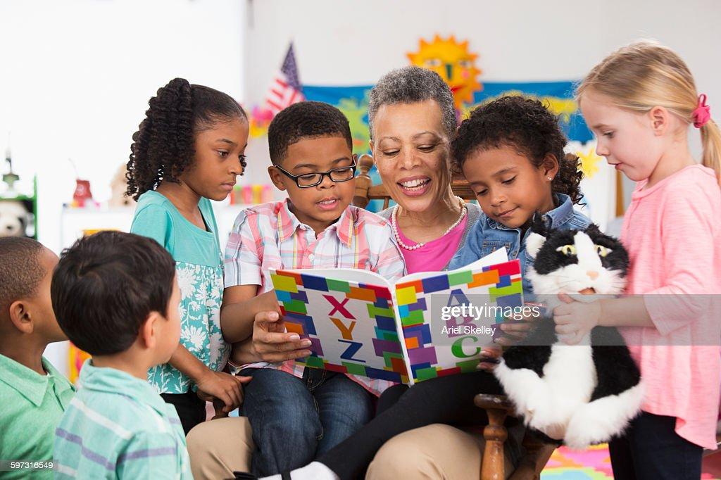 Kindergarten teacher reading to class : Stock Photo