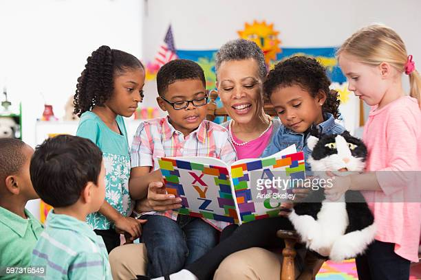 kindergarten teacher reading to class - preschool building stock pictures, royalty-free photos & images