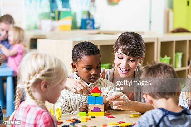 Kindergarten teacher with group of children in classroom