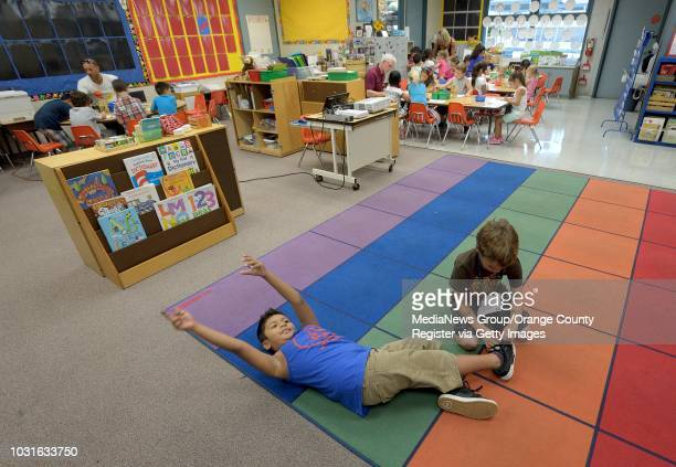Kindergartner Rune Spraker, right, ties the shoes of classmate Frankie Gonzalez during the fourth day of class at Marian Bergeson Elementary School...