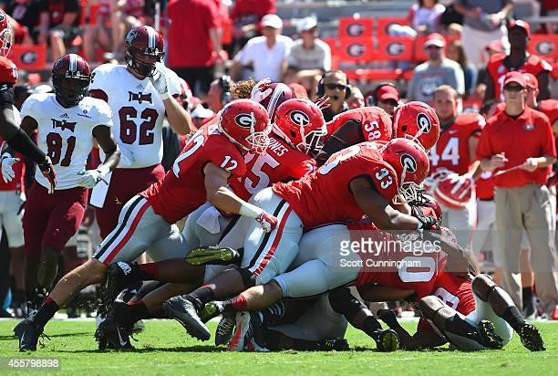 Kinderick Dent of the Troy Trojans is tackled by a swarm of Georgia Bulldogs defenders at Sanford Stadium on September 20 2014 in Athens Georgia