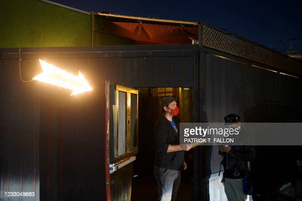 Kindrick Brooke checks a vaccination card outside Risky Business, a private members-only club, that was once The Other Door but closed during the...